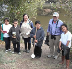 Docents and young students with water testing materials standing by slough